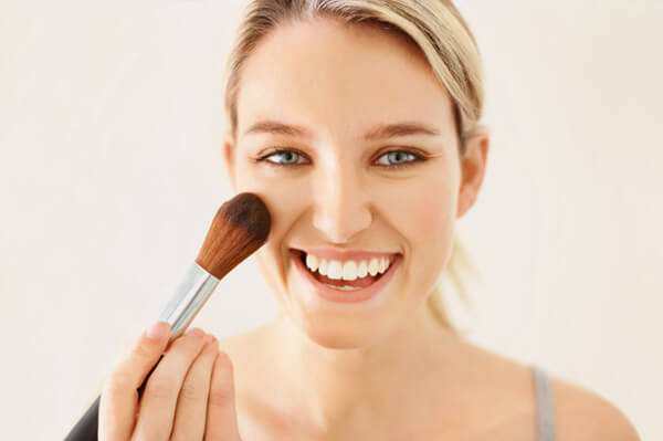woman-applying-powder-blush